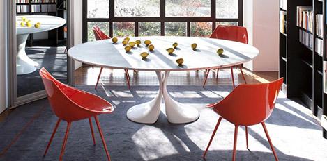 Ein runder Tisch mit orangenen Stühlen